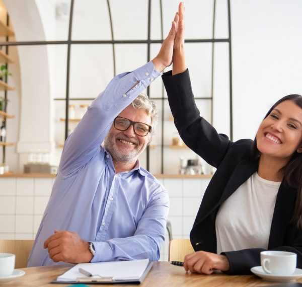 cheerful-young-and-mature-business-partners-giving-high-five-and-celebrating-success-sitting-at-table-with-documents-and-coffee-cups (1)